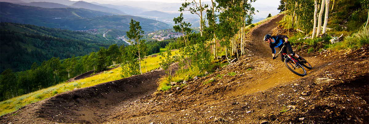a mountain biker mountain biking around a turn with the town of Park City below