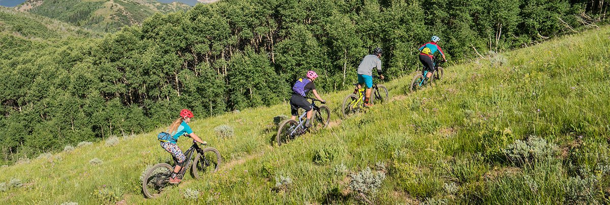 four mountain bikers with their backs facing cross country mountain biking on a trail