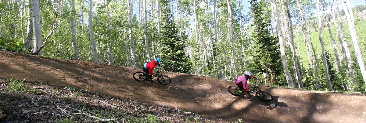 two mountain bikers turning on a berm in aspens
