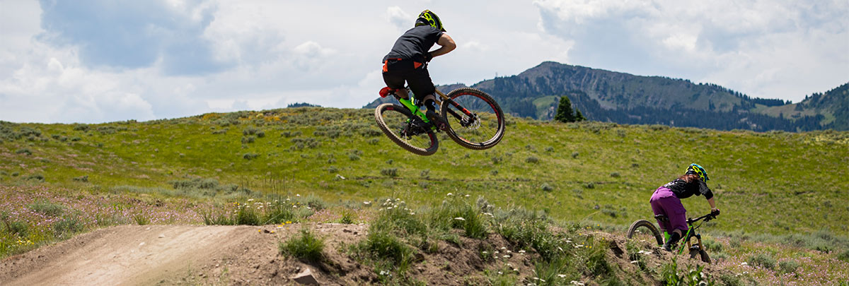 a mountain biker going off a jump with a second one in front with mountains in the background
