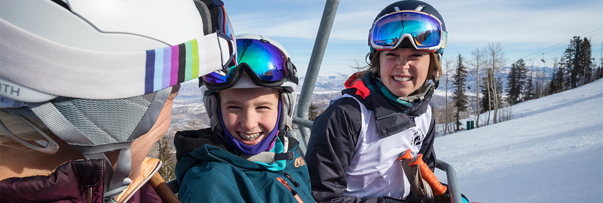 Kaylin Richardson smiling with two guests riding up a chairlift