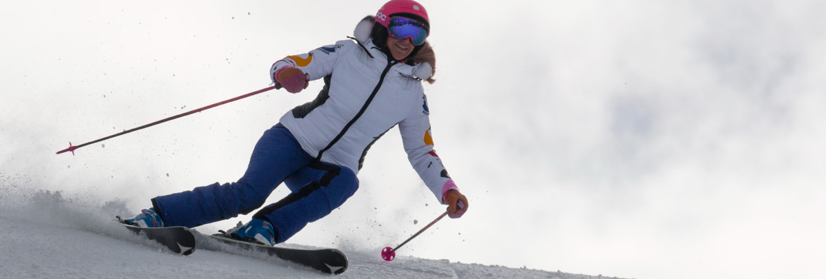 Shannon Bahrke smiling and skiing down a groomed ski run