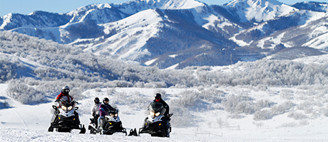 A group of people snowmobilng together with snowy mountains in the background