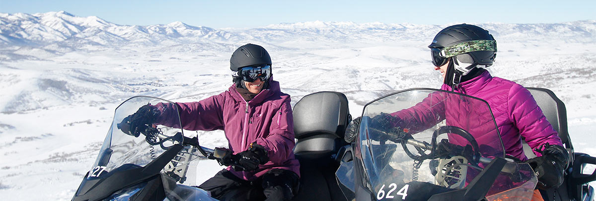 Two smiling women parked on snowmobiles with the snow covered mountains in the background