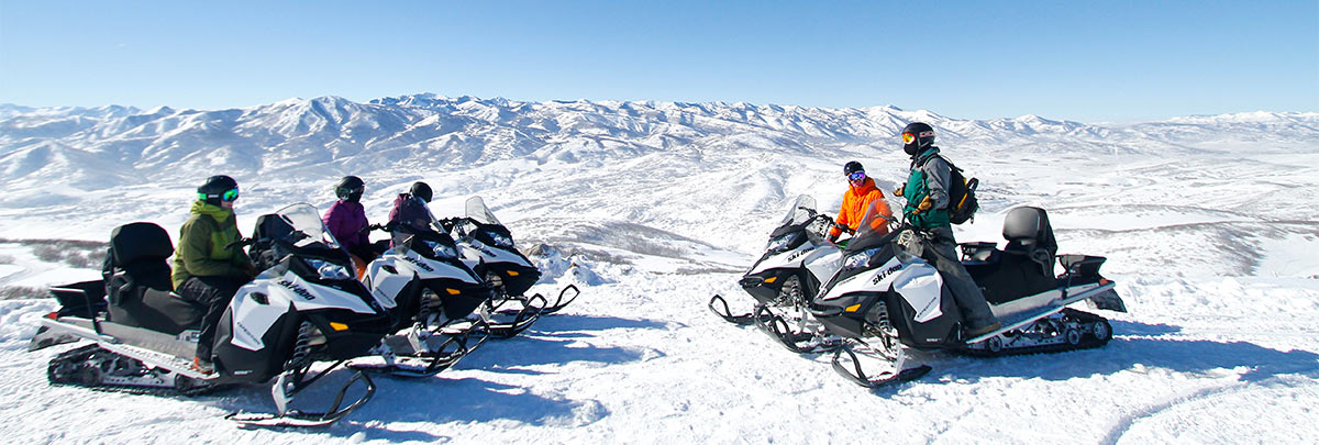 A group of four snowmobiliers with a guide parked at the top of a mountain overlooking Deer Valley Resort