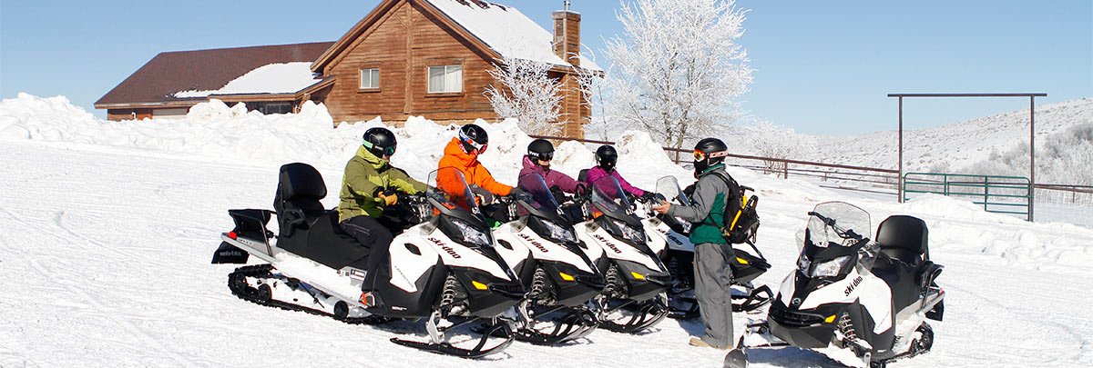 A group of snowmobiliers with a guide preparing to leave Garff Ranch to snowmobile