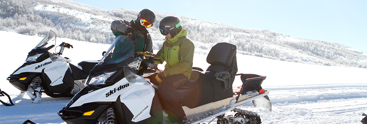 A guide instructing a snowmobiler how to use the snowmobile