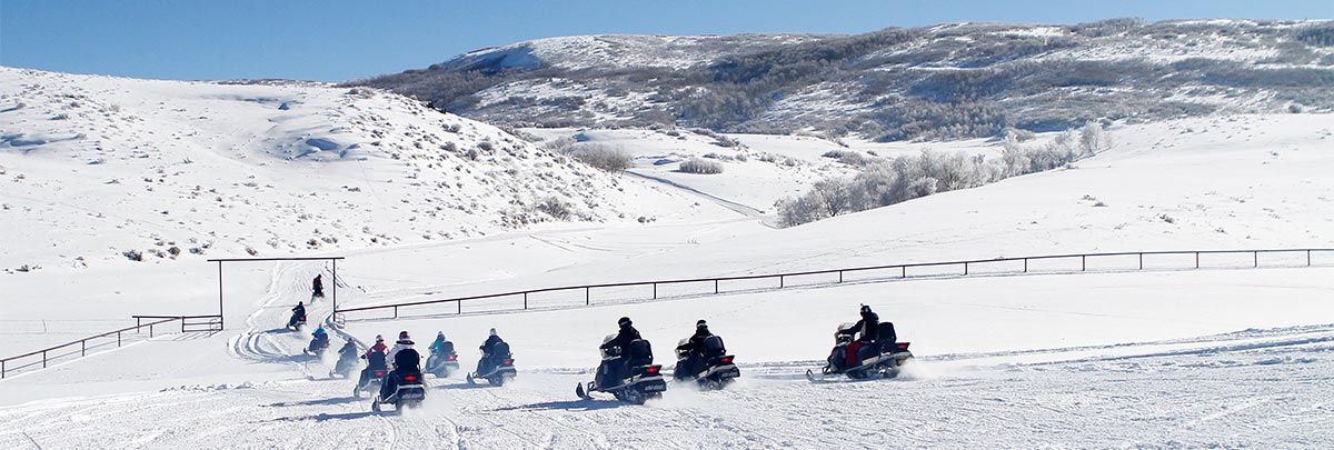 A group of 10 snowmobiliers leaving Garff Ranch with a guide