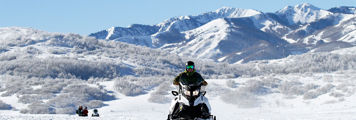 A snomobilier coming over a small hill with two snowmobilers in the background with the mountains
