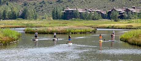 a group of people stand up paddle boarding in the ponds with The Lodges at Deer Valley in the background