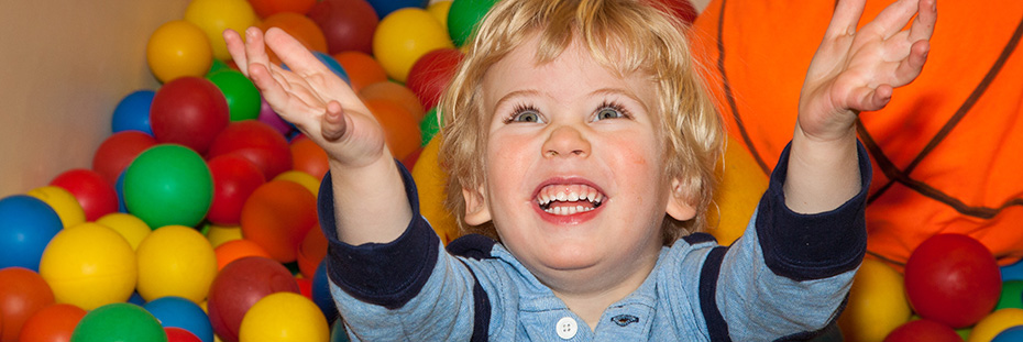 Child playing and smiling in a ball pit