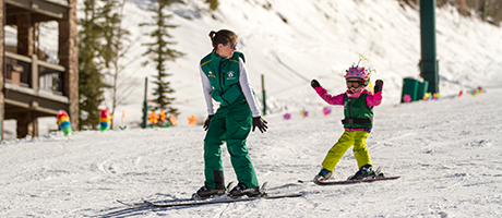 A small child following a ski instructor in Bambi Club