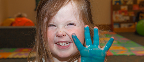 Little girl with blue paint on her hand
