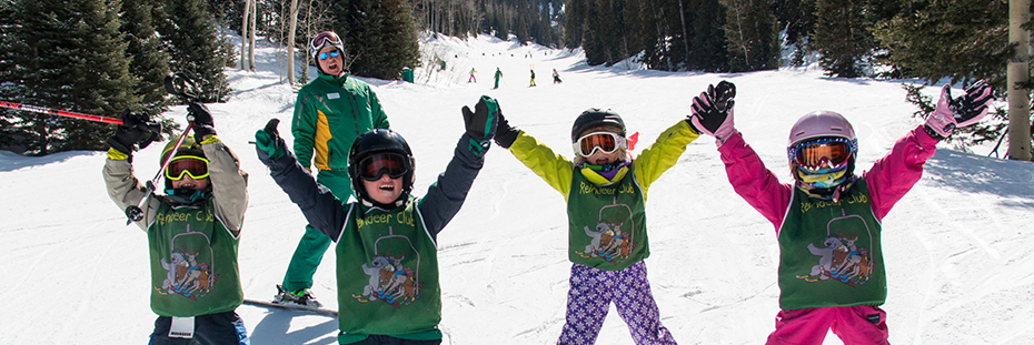 Group of four ski school students who have their hands up