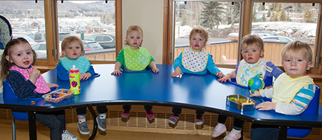 Group of six toddlers sitting around a table with bibs on