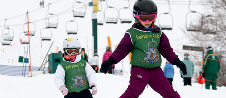 Two children with green Reindeer Club bibs on skiing