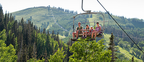 a family of four riding up a chairlift with the mountains in the background