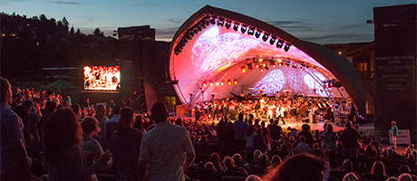 the Snow Park Outdoor Amphitheater venue with an audience listening to a concert with a sunset and mountains in the background