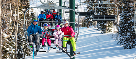 A family of four riding up a chairlift together