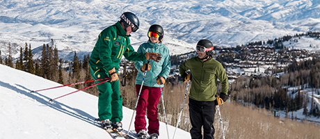 A ski instructor teaching a lesson to two guests