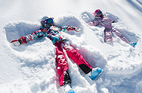 Image of four children in bright colored ski clothes