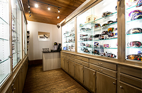 Image of guest looking at a pair of sunglasses and a store clerk helping