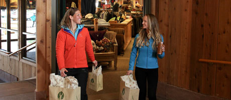 Two smiling ladies walking out of the Signatures store at Snow Park Lodge with shopping bags