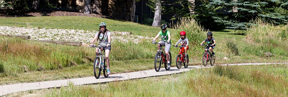 A counselor on a bike leading three campers on bikes on a bike path