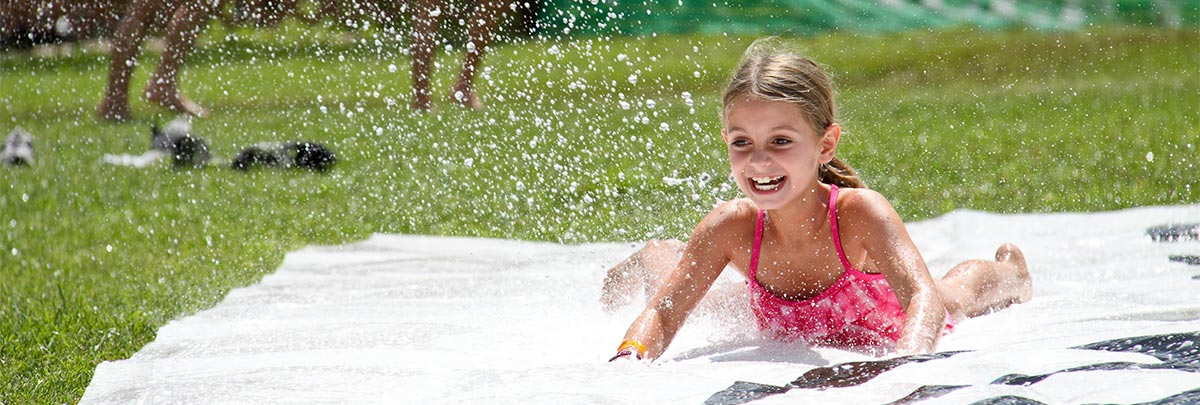 A little girl sliding down a slip n' slide smiling